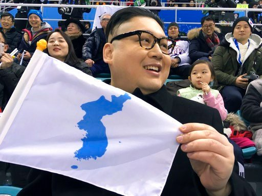 (AP Photo/Eric Talmadge, File). FILE - In this Feb. 14, 2018, file photo, a Kim Jong Un impersonator, calling himself only Howard X from Australia, holds a unification flag while attending the Korea-Japan women's ice hockey game at the 2018 Winter Olym...