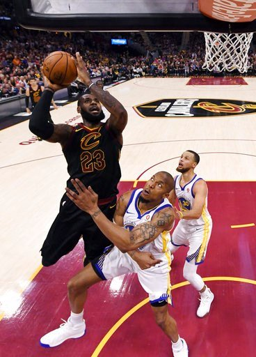 (Gregory Shamus/Pool Photo via AP). Cleveland Cavaliers' LeBron James shoots over Golden State Warriors' David West during the first half of Game 4 of basketball's NBA Finals, Friday, June 8, 2018, in Cleveland.