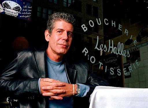 (AP Photo/Jim Cooper,File). FILE - This Dec. 19, 2001 file photo shows Anthony Bourdain, the owner and chef of Les Halles restaurant, sitting at one of the tables in New York. On Friday, June 8, 2018, Bourdain was found dead in his hotel room in France...