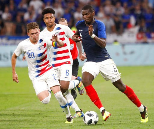 (AP Photo/Laurent Cipriani). CORRECTS TO McKennie NOT Mckennie - France's Paul Pogba, right, battles for the ball with United States' Will Trapp, left, and Weston McKennie during a friendly soccer match between France and USA at the Groupama stadium in...