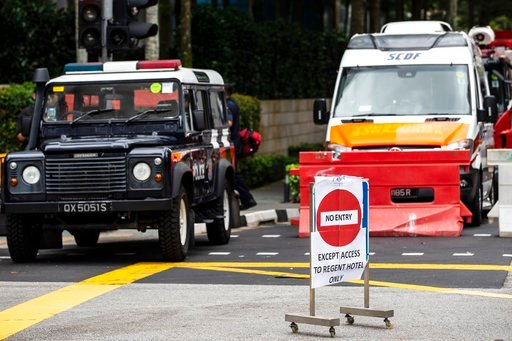 (AP Photo/Yong Teck Lim). Police vehicles block an entrance outside the St. Regis Hotel in Singapore, Sunday, June 10, 2018, ahead of the summit between U.S. President Donald Trump and North Korean leader Kim Jong Un.