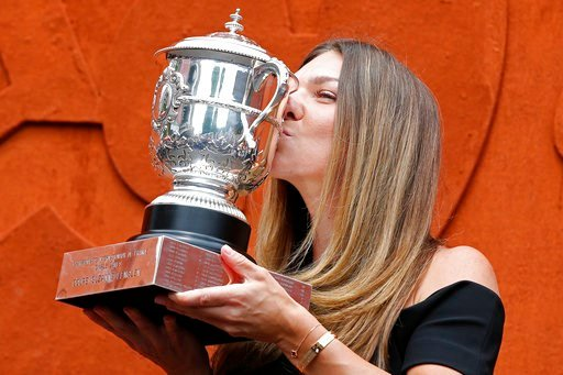 (AP Photo/Thibault Camus). Romania's Simona Halep kisses with the cup at the Roland Garros stadium, Sunday, June 10, 2018 in Paris. Halep won Saturday the French Open tennis tournament women's final.