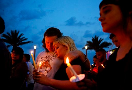 (AP Photo/David Goldman, File). FILE - In this June 13, 2016, file photo, Lucinda Rex, right, and Clarity Thorne embrace during a candlelight vigil downtown for the victims of a mass shooting at the Pulse nightclub in Orlando, Fla. Survivors and victim...