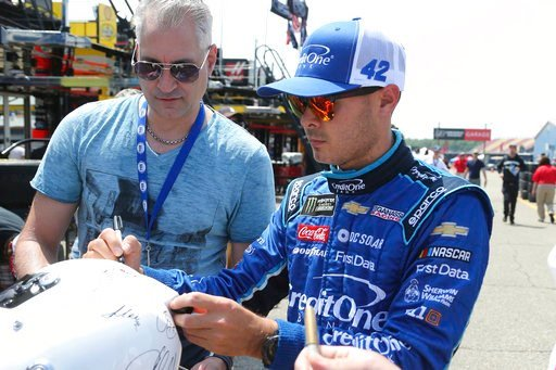 (AP Photo/Bob Brodbeck). NASCAR driver Kyle Larson signs autographs after practice for the NASCAR Cup Series auto race in Brooklyn, Mich., Fruday, June 8, 2018.