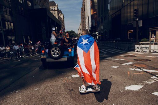(AP Photo/Andres Kudacki). FILE - In this June 11, 2017 file photo, a man rolls on a hover-board along Fifth Avenue during the National Puerto Rican Day Parade in New York.  Amid all the fun and celebration planned for this years parade on Sunday, June...