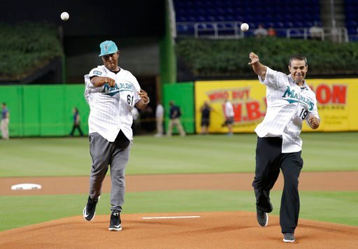 (AP Photo/Lynne Sladky). Former Florida Marlins players Livan Hernandez, left,  and Mike Lowell, right, throw ceremonial pitches before a baseball game between the Miami Marlins and San Diego Padres, Sunday, June 10, 2018, in Miami. The Marlins are cel...