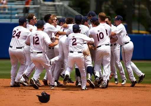 (Cyndi Chambers/The Gainesville Sun via AP). Auburn teammates mob Luke Jarvis after he hit an RBI-single to defeat Florida during an NCAA college super regional baseball game Sunday, June 10, 2018, in Gainesville, Fla.