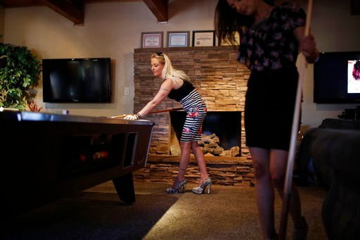 (AP Photo/John Locher). In this June 1, 2018, photo, prostitutes Destini Starr, right, and Paris Envy play pool while waiting for customers at the Love Ranch brothel in Crystal, Nev. A coalition of religious groups and anti-sex trafficking activists ha...