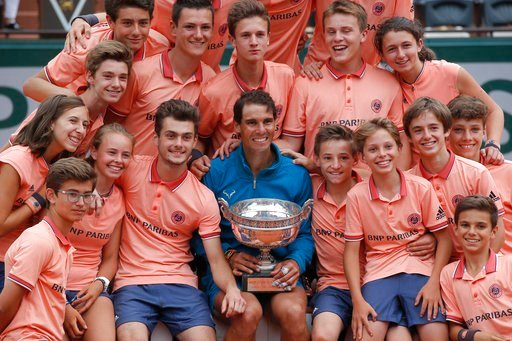 (AP Photo/Michel Euler). Spain's Rafael Nadal poses with ball girls and boys as he celebrates winning the men's final match of the French Open tennis tournament against Austria's Dominic Thiem in three sets 6-4, 6-3, 6-2, at the Roland Garros stadium i...