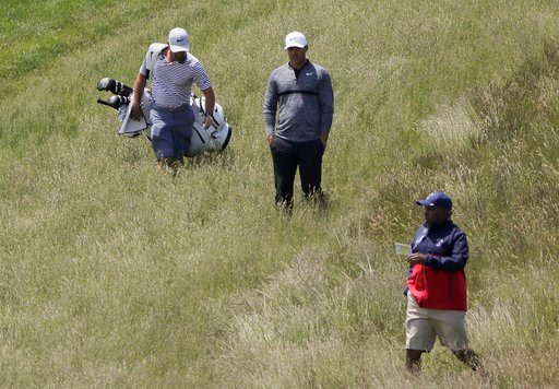 (AP Photo/Julie Jacobson). Brooks Koepka, center, lines up a shot from the rough along the 9th fairway during a practice round for the U.S. Open Golf Championship, Monday, June 11, 2018, in Southampton, N.Y.