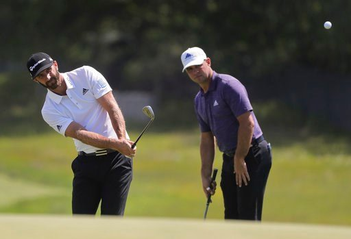 (AP Photo/Julie Jacobson). Dustin Johnson chips onto the second green as Gary Woodland looks on during a practice round for the U.S. Open Golf Championship, Monday, June 11, 2018, in Southampton, N.Y.