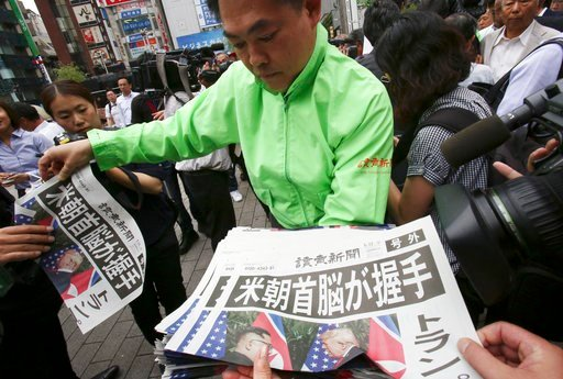 (AP Photo/Koji Sasahara). A staff of a Japanese news paper Yomiuri distributes an extra edition of the newspaper reporting about the summit between U.S. President Donald Trump and North Korean leader Kim Jong Un in Singapore, at Shimbashi Station in To...
