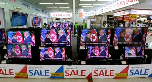 (AP Photo/Ahn Young-joon). TV screens shows U.S. President Donald Trump, right, meets with North Korean leader Kim Jong Un in Singapore during a news program, at Yongsan Electronic store in Seoul, South Korea, South Korea, Tuesday, June 12, 2018.