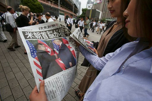 (AP Photo/Koji Sasahara). People look at an extra edition of the newspaper Yomiuri reporting about the summit between U.S. President Donald Trump and North Korean leader Kim Jong Un in Singapore, at Shimbashi Station in Tokyo, Tuesday, June 12, 2018.  ...