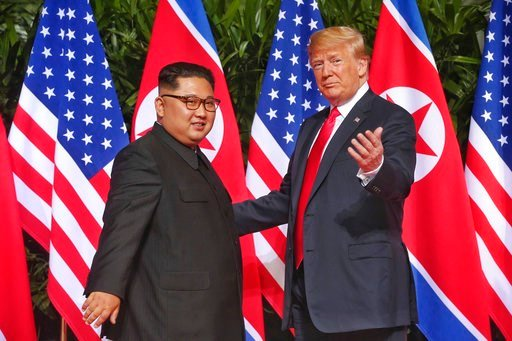 (Kevin Lim/The Straits Times via AP). U. S. President Donald Trump gestures toward the media with North Korea leader Kim Jong Un at the Capella resort on Sentosa Island Tuesday, June 12, 2018, in Singapore.