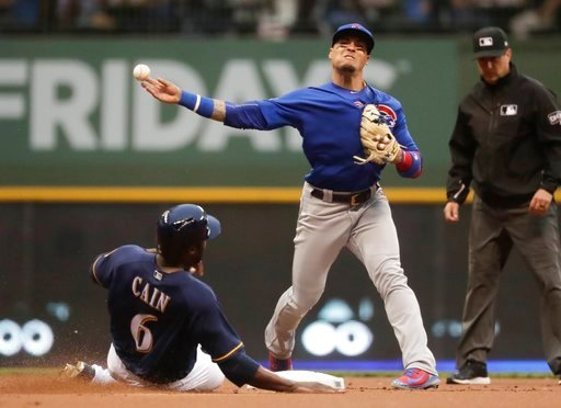 (AP Photo/Morry Gash). Milwaukee Brewers' Lorenzo Cain is out at second as Chicago Cubs' Javier Baez turns a double play on a ball hit by Christian Yelich during the first inning of a baseball game Monday, June 11, 2018, in Milwaukee.