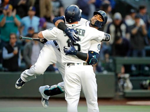 (AP Photo/Ted S. Warren). Seattle Mariners' Nelson Cruz, right, hugs teammate Kyle Seager after Cruz hit a two-run home run to score Jean Segura during the first inning of a baseball game against the Los Angeles Angels, Monday, June 11, 2018, in Seattle.