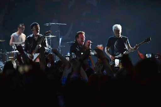 (Photo by Evan Agostini/Invision/AP). The Edge, left, Bono, Adam Clayton and drummer Larry Mullen Jr. of U2 perform during a concert at the Apollo Theater hosted by SiriusXM on Monday, June 11, 2018, in New York.