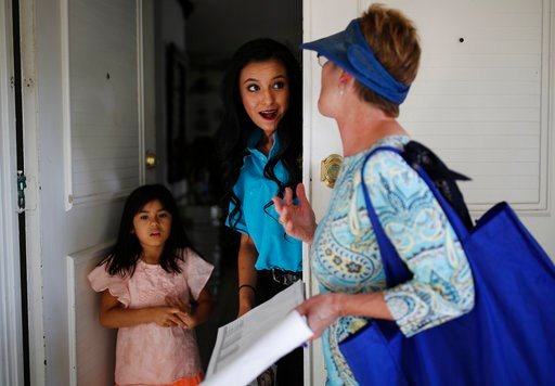 (AP Photo/John Locher). In this June 6, 2018, photo, Clark County Commission member Chris Giunchigliani, right, speaks with Susan Garcia, center, and Aileen Vides while campaigning in Las Vegas. The fiercest primary election battle in Nevada this year ...