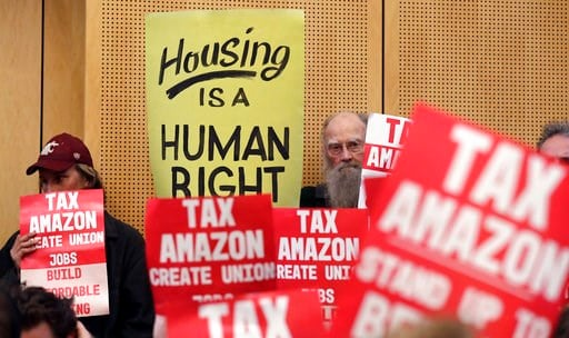 (AP Photo/Elaine Thompson, File). In this May 14, 2018, file photo, members of the public look on at a Seattle City Council before the council voted to approve a tax on large businesses such as Amazon and Starbucks to fight homelessness in Seattle.