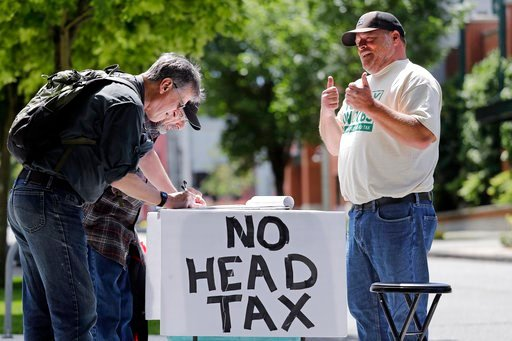 (AP Photo/Elaine Thompson). In this May 24, 2018, photo, paid signature gatherer John Ellard, right, gives thumbs-up as two men stop to sign petitions to put on the November ballot a referendum on Seattle's head tax, in Seattle.