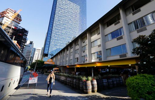 (AP Photo/Ted S. Warren, File). In this May 7, 2018, file photo, a pedestrian walks past the site at right in Seattle where Amazon.com has halted construction planning on a new 17-story tower as it awaits a tax vote from the Seattle City Council.