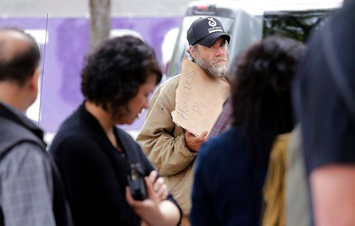 (AP Photo/Elaine Thompson). In this May 24, 2018, photo, Will Hartfield, who said he has been homeless about five years, stands on the sidewalk as people nearby line-up to buy lunch at a Dick's Drive-In restaurant in Seattle.