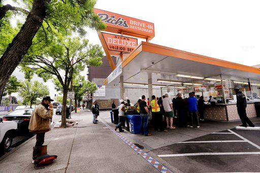(AP Photo/Elaine Thompson). In this May 24, 2018, photo, Will Hartfield, who said he has been homeless about five years, stands on the sidewalk and eats a meal given him as people nearby line-up to buy lunch at a Dick's Drive-In restaurant in Seattle.