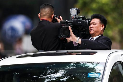 (AP Photo/Yong Teck Lim). North Korean journalists film the motorcade of North Korea leader Kim Jong Un as they leave the St. Regis Hotel on the way to the Capella Hotel in Singapore, Tuesday, June 12, 2018, where the summit between Kim and U.S. Presid...