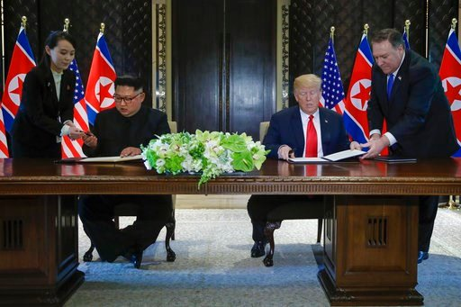(AP Photo/Evan Vucci). North Korea leader Kim Jong Un and U.S. President Donald Trump prepare to sign a document at the Capella resort on Sentosa Island Tuesday, June 12, 2018 in Singapore.