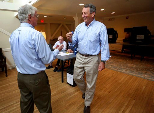 (Grace Beahm Alford/The Post And Courier via AP). Poll volunteer Tom Spain hands out stickers to former Gov, Mark Sanford after he cast his own ballot at Alhambra Hall polling station Tuesday, June 12, 2018, in Mt. Pleasant, S.C.