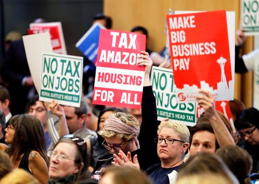 "(AP Photo/Ted S. Warren). People attending a Seattle City Council meeting hold signs that read ""Tax Amazon, Housing for All,"" and ""No Tax on Jobs"" listen to public comment on the debate over a possible council vote whether or not to repeal of a tax on ..."