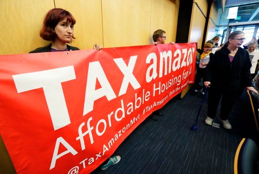 "(AP Photo/Ted S. Warren). Demonstrators opposing the repeal of a tax on large companies such as Amazon and Starbucks that was intended to combat a growing homelessness crisis hold a sign that reads ""Tax Amazon"" as they wait for the start of a Seattle C..."