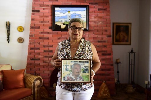 (AP Photo/Carlos Giusti). Nerybelle Perez poses with a portrait of her father, World War II veteran Efrain Perez, who died inside an ambulance after being turned away from the largest public hospital when it had no electricity or water, days after Hurr...