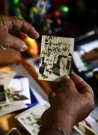 (AP Photo/Carlos Giusti). Nerybelle Perez holds a picture of her father, World War II veteran Efrain Perez, who died inside an ambulance after being turned away from the largest public hospital when it had no electricity or water, days after Hurricane ...
