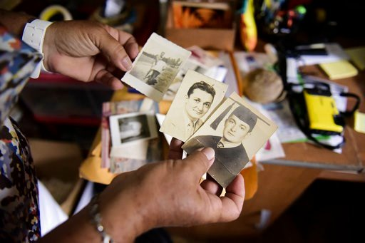 (AP Photo/Carlos Giusti). Nerybelle Perez holds several pictures of her father, World War II veteran Efrain Perez, who died inside an ambulance after being turned away from the largest public hospital when it had no electricity or water, days after Hur...