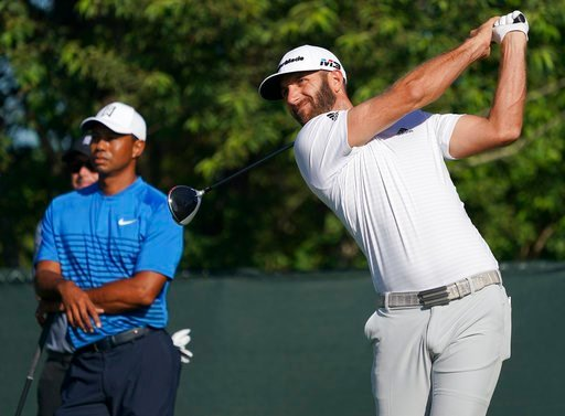 (AP Photo/Carolyn Kaster). Dustin Johnson hits off the fourth tee as Tiger Woods looks on during a practice round for the U.S. Open Golf Championship, Tuesday, June 12, 2018, in Southampton, N.Y.