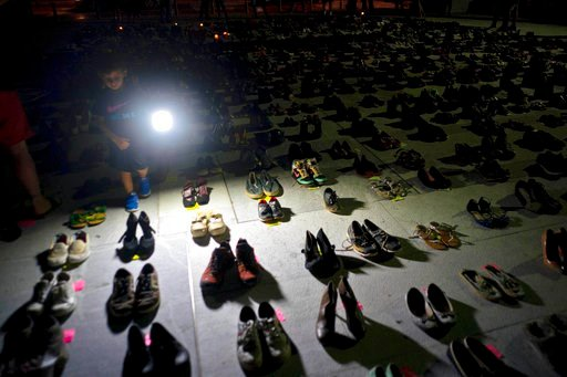 (AP Photo/Ramon Espinosa). FILE - In this Friday, June 1, 2018 file photo, a child shines a light on hundreds of shoes at a memorial for those killed by Hurricane Maria, in front of the Puerto Rico Capitol in San Juan. In June 2018, two bills were intr...