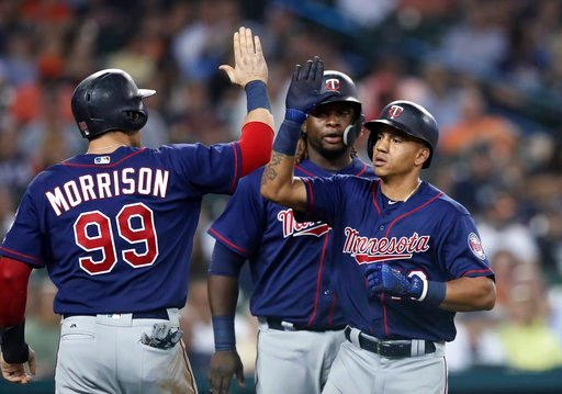 (AP Photo/Carlos Osorio). Minnesota Twins' Ehire Adrianza, right, is greeted by Logan Morrison (99) and Miguel Sano, rear, after they scored on Adrianza's grand slam during the seventh inning of a baseball game against the Detroit Tigers, Tuesday, June...