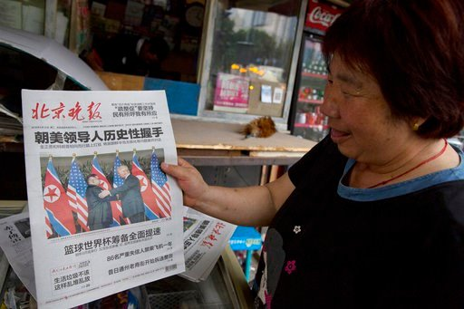 (AP Photo/Ng Han Guan, File). FILE - In this June 12, 2018, file photo, a newspaper vendor holds up a front page photo of the meeting in Singapore between U.S. President Donald Trump and North Korean leader Kim Jong Un at a newsstand in Beijing, China....