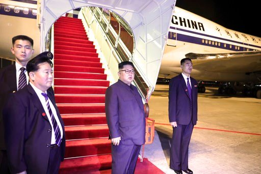(Ministry of Communications and Information, Singapore via AP). In this photo released by the Ministry of Communications and Information, Singapore, North Korean leader Kim Jong Un, center, stands before boarding the airplane, at Changi airport.