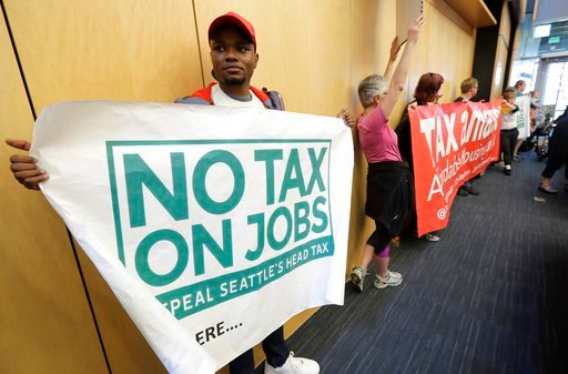 "(AP Photo/Ted S. Warren). A demonstrator in favor of the repeal of a tax on large companies such as Amazon and Starbucks that was intended to combat a growing homelessness crisis holds a sign that reads ""No Tax on Jobs"" as he waits for the start of a S..."