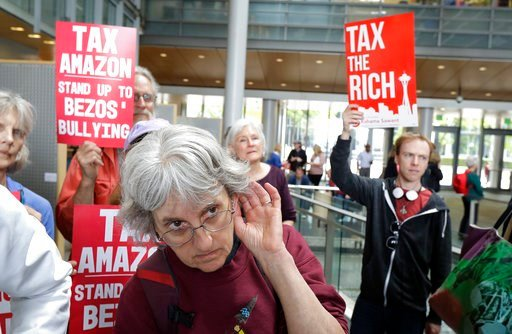 (AP Photo/Ted S. Warren). Annette Klapstein listens as Seattle City Council member Kshama Sawant speaks, Tuesday, June 12, 2018, at City Hall in Seattle. Sawant and other members of the Council were expected to vote Tuesday on whether or not to repeal ...