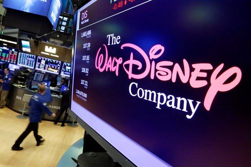 (AP Photo/Richard Drew, File). In this Aug. 8, 2017, file photo, The Walt Disney Co. logo appears on a screen above the floor of the New York Stock Exchange.