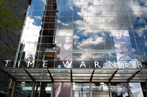 (AP Photo/Mark Lennihan, File). FILE - In this Oct. 24, 2016, file photo, clouds are reflected in the glass facade of the Time Warner building in New York. The judge presiding over the government's legal effort to block AT&T's purchase of Time Warn...