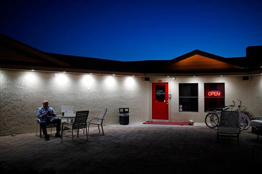 (AP Photo/John Locher). In this April 27, 2018, photo, owner Dennis Hof sits in front of the Love Ranch brothel in Crystal, Nev.
