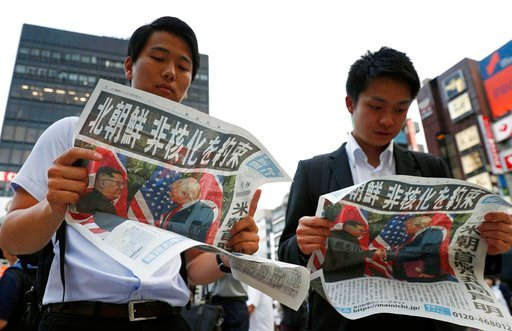 (Suo Takekuma/Kyodo News via AP). People look at the extra edition of  Japanese newspaper Mainichi Shimbun reporting the summit between U.S. President Donald Trump and North Korean leader Kim Jong Un in Singapore, at Shimbashi Station in Tokyo, Tuesday...