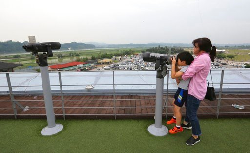 (AP Photo/Ahn Young-joon). A mother holds her son as he looks through binoculars towards North Korea at the Imjingak Pavilion in Paju near the border village of Panmunjom, South Korea, Wednesday, June 13, 2018. While South Koreans cheered with hope and...