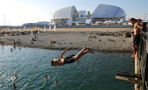 (AP Photo/Andre Penner). A boy jumps into the black sea in front of the Fisht stadium, which will host some 2018 World Cup matches in Sochi, Russia, Monday, June 11, 2018.