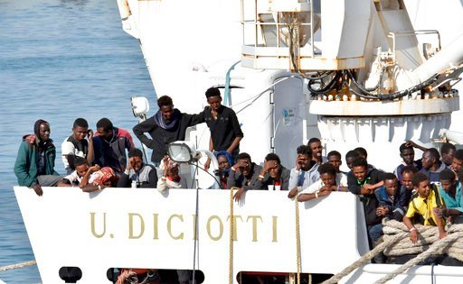 "(Orietta Scardino/ANSA via AP). Migrants wait to disembark from an Italian Coast Guard vessell ""Diciotti"" as it docks at the Sicilian port of Catania, southern Italy, Wednesday, June 13, 2018. The vessel docked in Catania with 932 migrants aboard in a ..."